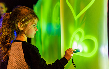 Girl with flashlight drawing on green lit up wall